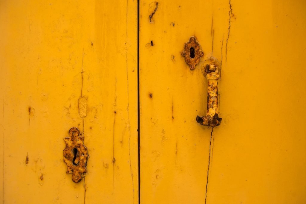Rusty vintage keyhole on a yellow wooden door